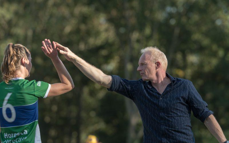 Coach Leo van den Bos geeft een high five aan Christel Zwanenburg tijdens de wedstrijd tegen VEO.
